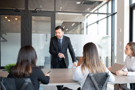 Mature businessman addressing to team of professionals in meeting room
