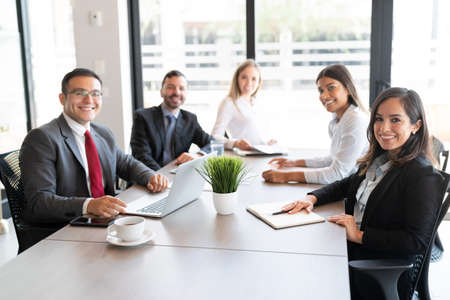 Portrait of multi-ethnic group of businesspeople sitting around conference table