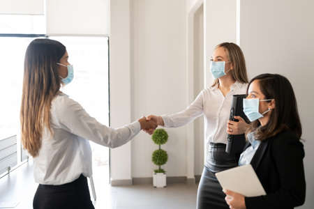 Businesspeople wearing protective face masks shaking hands in office during pandemic