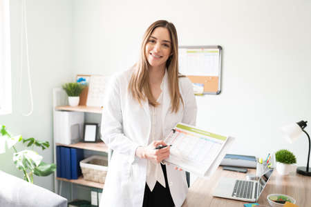 Friendly Caucasian woman working as a nutritionist and holding a meal plan and diet in her office and making eye contact