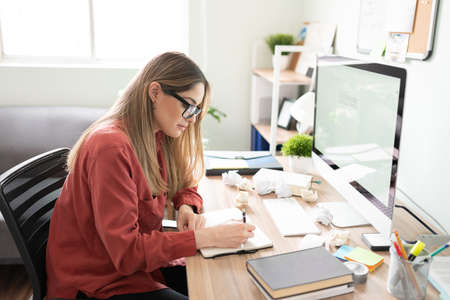 Beautiful woman and writer taking some notes in a notepad and filling the desk with crumpled paged due to her lack of inspiration
