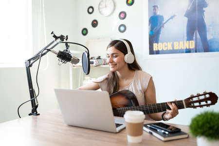 Beautiful Hispanic singer songwriter playing a guitar and recording a song for her online show