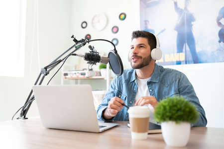 Portrait of a handsome Hispanic blogger and radio host recording a live podcast in a studio and enjoying his job Stock Photo