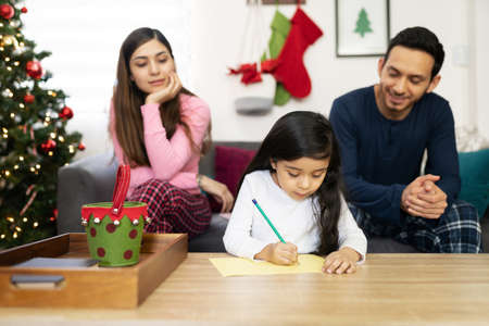 Little girl sitting with her parents at home and writing a letter to Santa before Christmas 版權商用圖片
