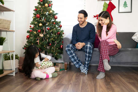 Couple of Hispanic parents wearing pajamas and watching their little girl open a present next to the Christmas tree