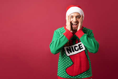 Hispanic man with ugly sweater opening his mouth and looking surprised about some awesome Christmas sale
