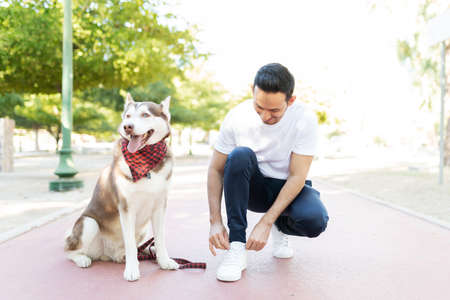 Hispanic dog owner tying his shoelaces in the park's running track next to his sitting husky dog