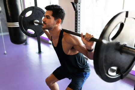 Side view of a determined and athletic young man fixed on doing a squat and lifting a heavy barbell at the gym Banco de Imagens