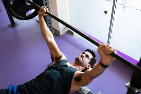 Fit young man seen from above fixed on lifting a heavy barbell and lying on a gym bench Banco de Imagens