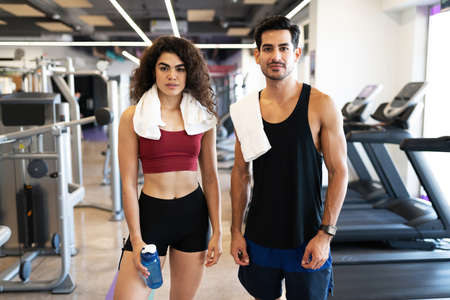 Fitness latin couple taking a break from their weightlifting training and cardio exercises at the fitness club