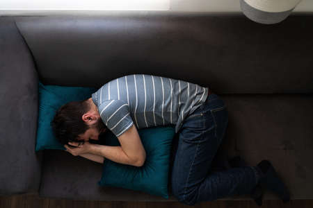 Top view of an adult man curled up on his home couch crying and looking sad and miserable