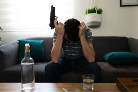Hopeless hispanic man with depression and anxiety and suicidal thoughts. Male adult sitting in his home and holding a gun in front of an alcohol bottle