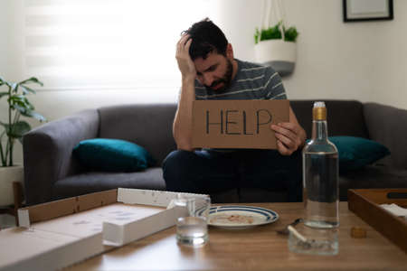 Depressed and alcoholic latin adult man sitting alone on the sofa and holding a sign with help written on it