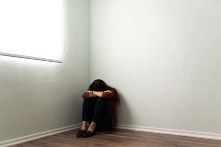 Grieving young woman sitting alone at a home corner. Depressed woman hugging her kness and hiding her face