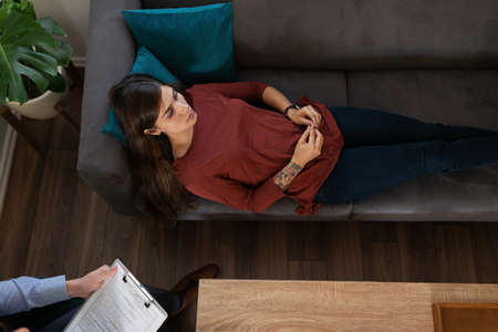 Sad latin young female patient seen from above lying on the couch during a pshycological therapy session with a male pshychiatrist