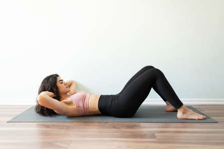 Athletic and fit young hispanic woman strengthening her core muscles with abdominal crunches