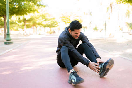 Latin guy in his 20s in sportswear suffering of a foot injury in the running track of the park
