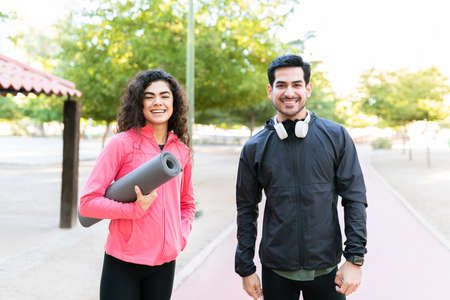 Beautiful young woman and attractive young man smiling and happy to start their training workout in the park. Couple carrying an exercise mat and headphones