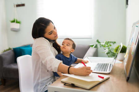 Young mother working at home office on a laptop talking on phone and making notes while holding her baby boy