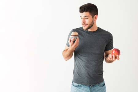 Fit latin young guy with a healthy diet holding an apple and a chocolate cupcake, handsome guy choosing to eat a pastry Stock Photo