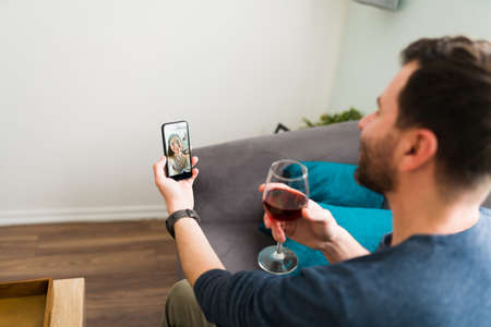 Good-looking couple in a relationship making a toast with a glass of wine during a video call for their online romantic date