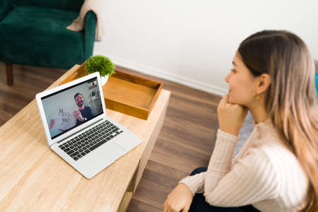 Beautiful woman watching her boyfriend on the screen of her laptop during a video call. Handsome guy holding a miss you sign to her long-distance girlfriend 写真素材
