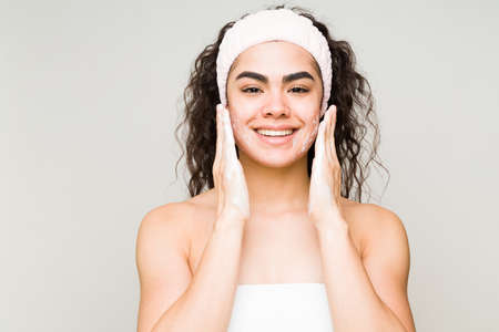 Happy beauty model wearing a towel and a headband and washing her face with a facial cleanser and soap Stock fotó