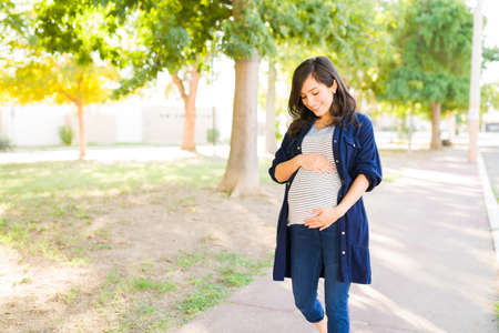 Attractive pregnant woman looking lovingly at her belly. Expectant mother staying active by taking a walk outdoors