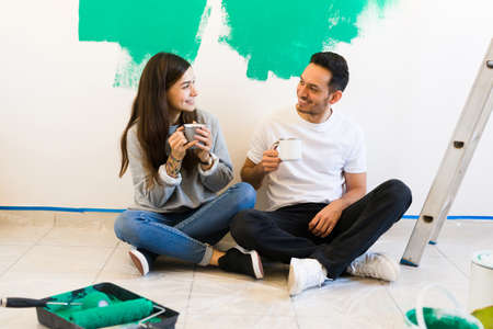 Girlfriend and boyfriend looking lovingly at each other while holding cups of coffee. Beautiful couple resting from painting the walls of their home