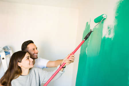 Happy married couple holding together a paint roller to paint green the white walls of their newly bought house
