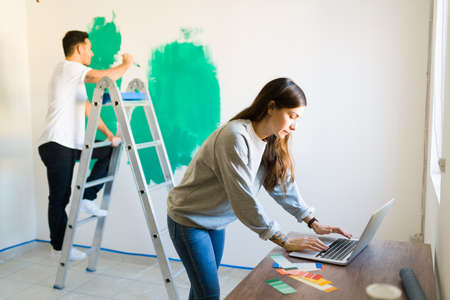 Girlfriend in her 20s searching for painting and decorating tips on the web while her handy boyfriend stands in a ladder with a paintbrush