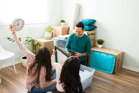 Young parents and daughter unpacking from a plastic container box after moving into a new house. Hispanic family deciding where to put their stuff and furniture