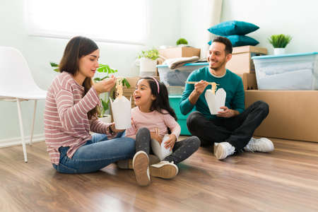 Attractive young woman feeding her cute daughter with chinese food. Happy family taking a break from unpacking and eating lunch together in moving day