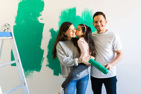 Joyful family painting and redecorating their new home. Elementary girl kissing her mom and the smiling dad holding a paint roller