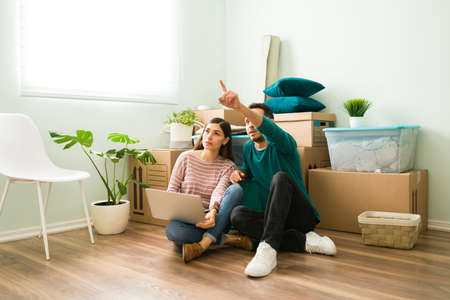 Young married couple planning on a laptop how to decorate and arrange the furniture on their new living room space Reklamní fotografie