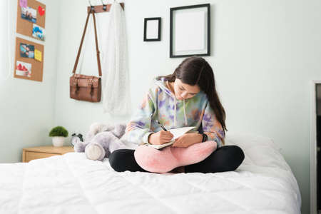Thoughtful young teen girl in her bedrrom writing about her day on a diary while sitting in bed. Beautiful teen girl pouring her dreams and thoughts in a notebook