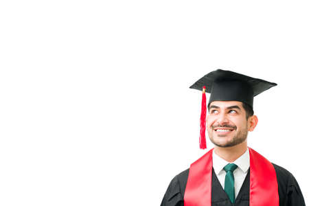 Handsome latin man in his 20s with a gown and cap looking up to copy space. Young graduate thinking and dreaming about his bright future after graduating from university