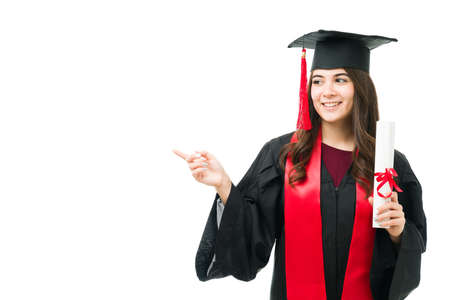 Beautiful caucasian young woman feeling happy after receiving her university diploma during the graduation ceremony and pointing to copy space