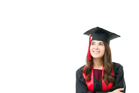 Beautiful woman in her 20s with a gown and cap looking up to copy space. Thoughtful young graduate thinking and dreaming about her bright future after graduating from university