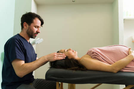 Side view of a pregnant woman lying on a massage table and relaxing at the spa. Male therapist rubbing the head of an expectant mother
