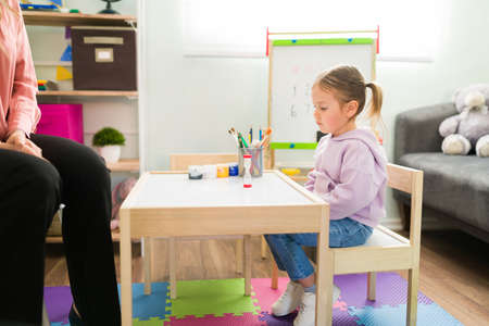 Beautiful elementary girl sitting on a kid's table in the therapist's office and looking at an hourglass. Caucasian little girl learning about discipline and self-control
