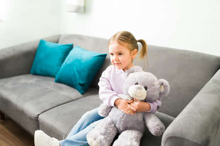 Beautiful little girl sitting in the sofa of her psychologist's office. Caucasian girl hugging a teddy bear and talking with her child therapist Reklamní fotografie
