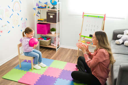 Beautiful girl smiling while holding a ball during a child therapy session. Female therapist clapping and proud of a preschool girl Banque d'images