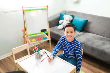 Portrait of an adorable elementary boy drawing at his psychologist's office. Happy little boy smiling while doing art therapy