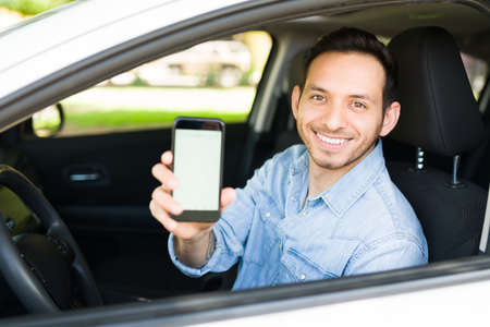Portrait of an hispanic man in his 30s holding a smartphone while sitting on the driver's seat. Male taxi driver working on a ride sharing app