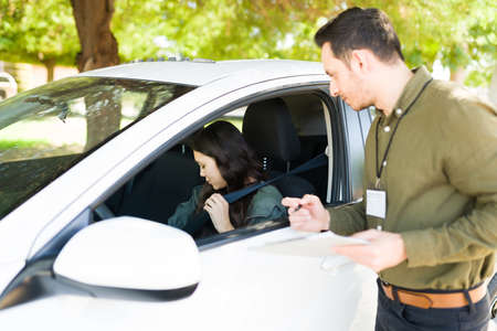 Male instructor guiding a teenage girl during her exam to get a driver's licence. Hispanic man telling an adolescent girl to put on her seatbelt