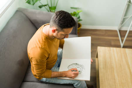 Top view of a handsome man in his 30s sketching with a pencil on a notebook. Latin man with a drawing hobby during a leisure day