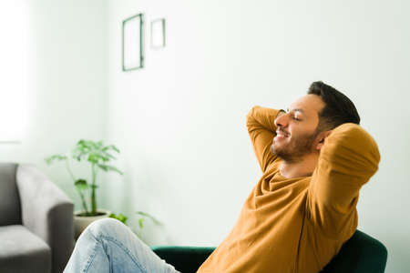Happy handsome man sitting in his living room. Man with good mental health relaxing with his eyes closed and the hands behind the head