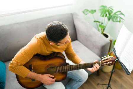 Latin man looking at the chord on his acoustic guitar while playing a song. Handsome male musician making new music during a leisure time 版權商用圖片