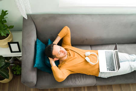 Top view of a calm hispanic man lying and relaxing on the sofa with his eyes closed while listening to meditation music on his laptop 版權商用圖片